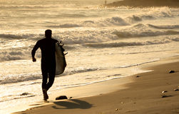 Silhouette of a surfer. At sunset running down the beach Stock Images