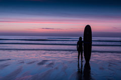 Silhouette of surfer on beach holding surfboard at sunset. Silhouette of a surfer on coast in the evening light stock images