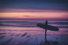 Silhouette of surfer on beach holding surfboard at sunset. Silhouette of a surfer on coast in the evening light Royalty Free Stock Images