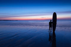 Silhouette of surfer on beach holding surfboard at sunset. Silhouette of a surfer on coast in the evening light royalty free stock photography