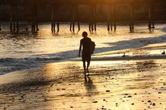 Silhouette of surfer on beach at sunset. Male surfer carries his board on the beach near a pier at sunset, Capitola, CA Royalty Free Stock Image