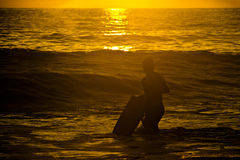 Silhouette of surfer with a board on a sunset Stock Photos