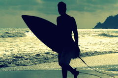 Silhouette of surfer with a board on a sunset evening in Manuel Antonio's National Park Costa Rica. Silhouette of surfer with a board on a sunset evening in Royalty Free Stock Photography