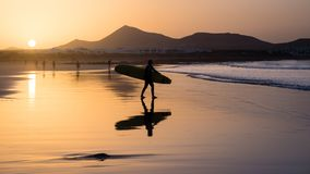 Silhouette of a Surfer on Famara beach at sunset stock photo