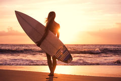 Silhouette surfer girl on the beach at sunset stock photography