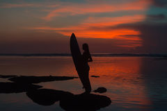 Silhouette of surfer girl with surfboard on tropical beach Royalty Free Stock Photos