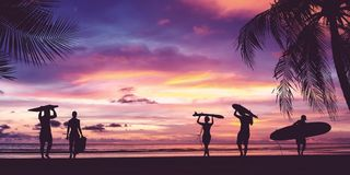Silhouette of surfer people carrying surfboard. Silhouette of surfer people carrying their surfboards on sunset beach. Panoramic soft style with vintage filter Royalty Free Stock Photography