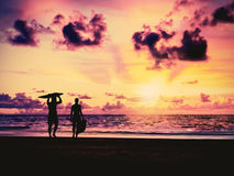 Silhouette Of surfer people. Carrying their surfboard on sunset beach, vintage filter effect Royalty Free Stock Photo