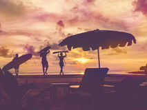 Silhouette of surfer people. Carrying their surfboard on sunset beach, vintage filter effect with soft style Royalty Free Stock Photos