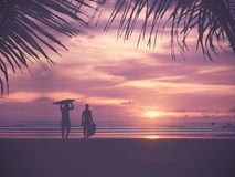 Silhouette Of surfer people. Carrying their surfboard on sunset beach, vintage filter effect with soft style Stock Photos