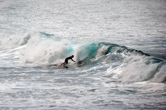 WAIMEA BEACH, OAHU, HAWAII/UNITED STATES - JANUARY 30, 2015: Silhouette of a surfer riding a wave royalty free stock photo