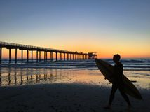Silhouette of a surfer at Scripps Pier in La Jolla, California. Male surfer walking by Scripps Pier at sunset in La Jolla, California, USA. Taken 3/24/2016 Stock Photo