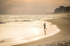 Silhouette of surfer walking on the beach during sunset. In Barra da Tijuca beach, Rio de janeiro Royalty Free Stock Photos