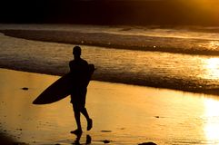 Silhouette of surfer at a yellow sunset royalty free stock photography
