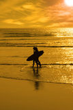 Silhouette of surfing couple walking from the sea Stock Photos