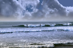 Silhouette of surfing couple walking from the sea Stock Photography