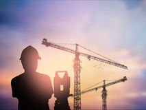 Silhouette survey engineer working  in a building site over Blur Stock Photography