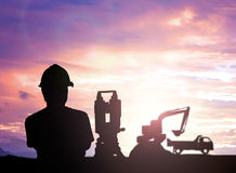 Silhouette survey engineer working  in a building site over Blur Stock Photo