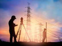 Silhouette survey engineer working  in a building site over Blur Stock Photos
