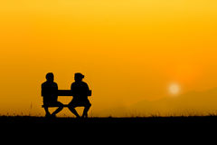 A silhouette of sweetheart on the bench. In sunset Royalty Free Stock Photo