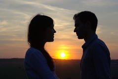 Silhouette sweethearts at sunset. In a field Stock Photo