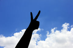 Silhouette of Symbol of victory. Hand under blue sky Stock Photo