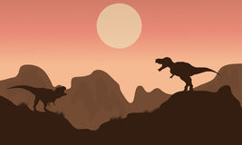 Silhouette of T-rex in cliff with sun Royalty Free Stock Photos