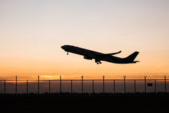 Silhouette takeoff plane while sunset Stock Image