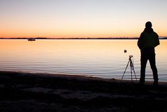 Silhouette of tall nature photographer at tripod taking picture on beach at sunset Royalty Free Stock Images