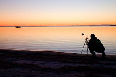 Silhouette of tall nature photographer at tripod taking picture on beach at sunset Stock Images