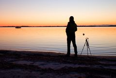 Silhouette of tall nature photographer at tripod taking picture on beach at sunset Stock Photography
