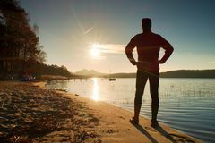 Silhouette of tall sportsman on decline seeing over bay to sun Stock Images