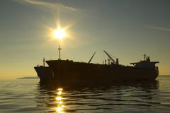 Silhouette tanker on sunset background Stock Photo