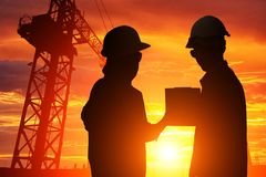 Silhouette Teams engineer looking construction. Worker in a building site at sunset Stock Photo