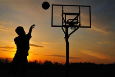Silhouette of Teen Boy shooting a Basketball. At Sunset Royalty Free Stock Images