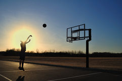 Silhouette of a Teen Boy shooting a Basketball. At Sunset, copy space Stock Photography