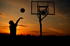 Silhouette of a Teen Boy shooting a Basketball. At Sunset, copy space Royalty Free Stock Photos