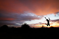 Teen jumping in sunset for fun Royalty Free Stock Photography