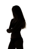 Silhouette of teenage girl with arms crossed Stock Photo