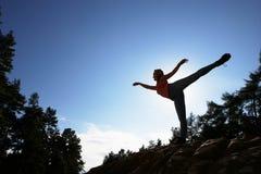 Silhouette Of Teenage Girl Balancing On Rock Stock Photography