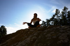Silhouette Of Teenage Girl Meditating Outdoors Stock Photo
