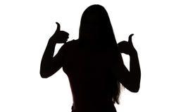 Silhouette of teenage girl with thumbs Stock Image