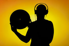 Silhouette of a teenager who holds the LP in front of yellow background Stock Photos