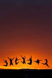Silhouette of teenagers jumping in sunset Stock Photos