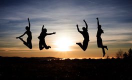 Teenagers jumping in sunset for fun Royalty Free Stock Photos