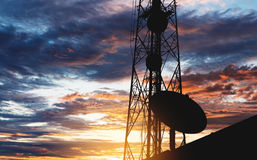 Silhouette Telecommunication tower with Satellite dish, under sunset sky stock photos