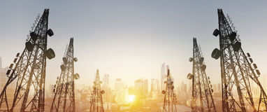 Silhouette, telecommunication towers with TV antennas and satellite dish in sunset, with double exposure city in sunrise backgroun. Silhouette, telecommunication Stock Photography