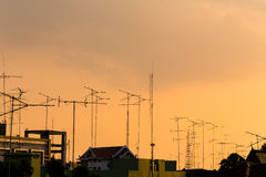 Silhouette, telecommunication towers with TV antennas and satellite dish in sunset. Many home TV antennas and satellite mounted stock photos
