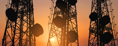 Silhouette, telecommunication towers with TV antennas and satellite dish in sunset, panorama composition Stock Images