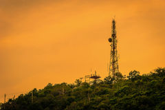 Silhouette telecommunications antenna for mobile phone. At sunset Stock Photography